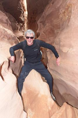 Father climbing over a chockstone in Little Wild Horse Canyon